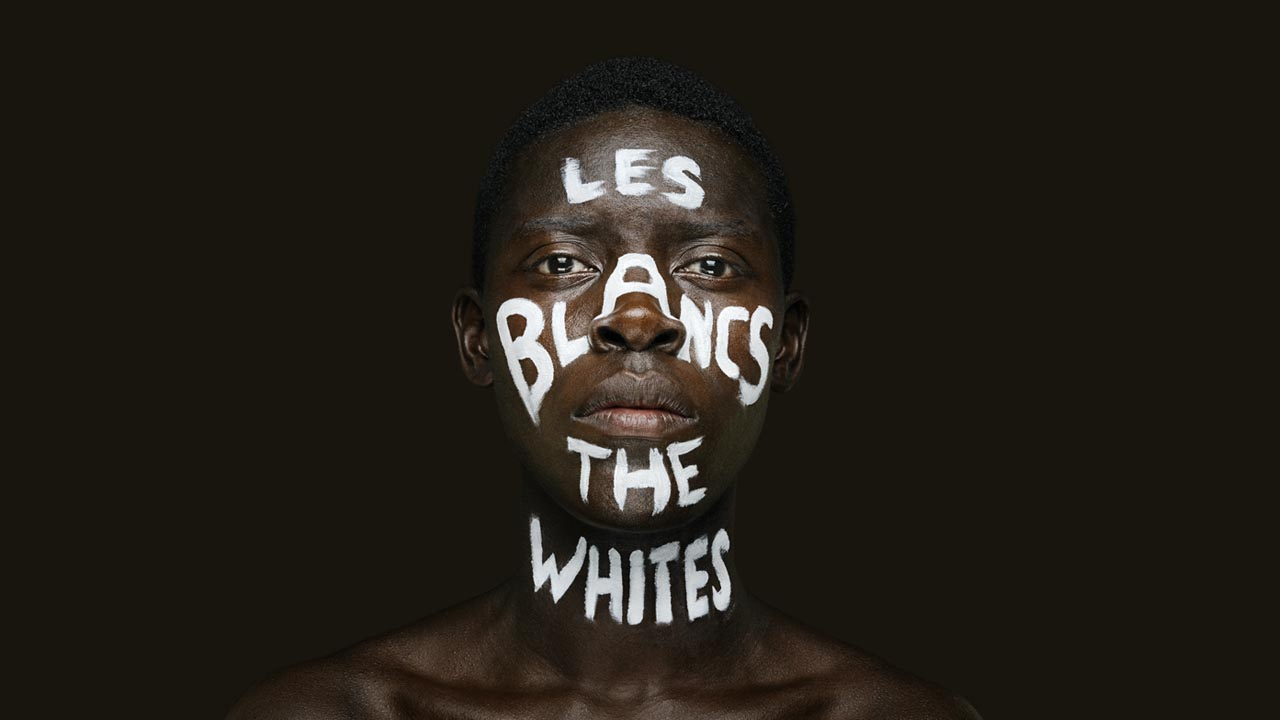 A Black man;s face with the words— Les Blancs The Whites— witten on his face in white paint.