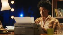 Photo of Samira Wiley working at an electric typewriter, enacting Lorraine Hansberry in a scene from HBO Max's four-part docuseries, EQUAL.